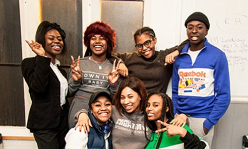 A group of young people strike a pose for the camera at Reaching Higher