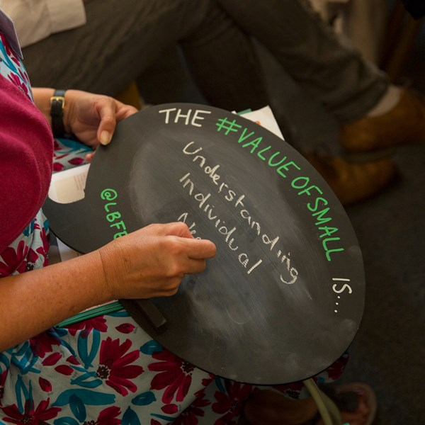 Woman writes on a Lloyds Bank Foundation #ValueOfSmall sign