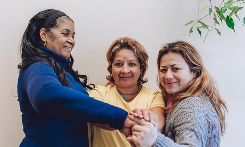 Three women at Latin American Women's Rights Service hold hands
